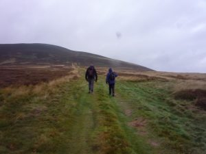 Dr Eila Williamson and Dàibhidh Grannd beginning the walk up Dirrington Great Law Photo Dr Simon Taylor.